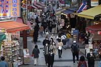 People wearing face masks walk through a shopping street in Tokyo on Nov. 19, 2020. (AP Photo/Hiro Komae)