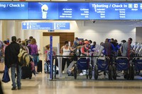 Holiday travelers check in at kiosks near an airline counter at Orlando International Airport on Nov. 24, 2020, in Orlando, Fla. (AP Photo/John Raoux)