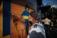 A soccer fan kisses a poster of Diego Maradona at the entrance of the Boca Juniors stadium, known as La Bombomera, in Buenos Aires, Argentina, Wednesday on Nov. 25, 2020. (AP Photo/Natacha Pisarenko)