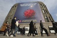 People wearing face masks walk under a banner emphasizing an enhanced social distancing campaign in front of Seoul City Hall in Seoul, South Korea, on Nov. 25, 2020. (AP Photo/Ahn Young-joon)