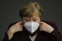 German Chancellor Angela Merkel adjusts her face mask as she arrives for a parliament session about German government's policies to combat the spread of the coronavirus and COVID-19 disease at the parliament Bundestag, in Berlin, Germany, on Nov. 26, 2020. (AP Photo/Markus Schreiber)