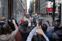 People attempt to take photos as the last floats that are part of the modified Macy's Thanksgiving Day Parade move away in New York, on Nov. 26, 2020. Due to the pandemic, crowds of onlookers were not allowed to attend the annual parade. (AP Photo/Craig Ruttle)