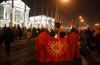 Two men hold the old national flag as opposition supporters gather to protest the leftist government policy towards Bulgaria, in front of the government building in Skopje, North Macedonia, on Nov. 26, 2020. (AP Photo/Boris Grdanoski)
