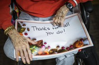A nursing home resident holds a sign addressed to the staff before a small Thanksgiving Day parade with nurses, other staff and residents at the Hebrew home at Riverdale in the Bronx, on Nov 26, 2020, in New York.(AP Photo/Eduardo Munoz Alvarez)