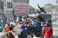 A farmer drives a tractor into a barricade in an attempt to remove it, at the border between Delhi and Haryana state, on Nov. 27, 2020. (AP Photo/Manish Swarup)
