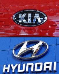 This combination of file photos shows the logo of Kia Motors during an unveiling ceremony on Dec. 13, 2017, in Seoul, South Korea, top, and Hyundai logo on the side of a showroom on April 15, 2018, in the south Denver suburb of Littleton, Colo., bottom. (AP Photo)