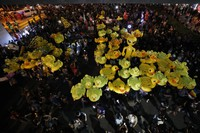 Inflatable yellow ducks, which have become good-humored symbols of resistance during anti-government rallies, are lifted over a crowd of protesters, on Nov. 27, 2020 in Bangkok, Thailand. (AP Photo/Sakchai Lalit)