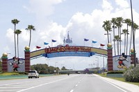 In this July 2, 2020, file photo, cars drive under a sign greeting visitors near the entrance to Walt Disney World, in Lake Buena Vista, Fla. (AP Photo/John Raoux)