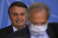 Brazil's President Jair Bolsonaro smiles behind his Economy Minister Paulo Guedes during a ceremony on a program to increase public sector efficiency at the Planalto presidential palace, in Brasilia, Brazil, on Nov. 26, 2020 (AP Photo/Eraldo Peres)