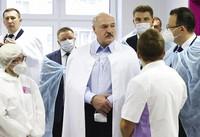 Belarusian President Alexander Lukashenko, centre, listens to medics as he visits a transfusiology center in Minsk, Belarus, on Nov. 27, 2020. (Maxim Guchek/BelTA Pool Photo via AP)