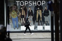 In this file photo dated on Nov. 20, 2020, a woman wearing a face mask walks past mannequins wearing face masks in the window of a temporarily closed branch of the Topshop women's clothing chain during England's second coronavirus lockdown, in London. (AP Photo/Matt Dunham)