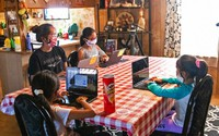 The Begaye sisters do their schoolwork at their home in Blue Gap, Ariz., on Sept. 24, 2020. On the Navajo Nation, a high school senior spends six hours most days doing homework in a car next to a school bus turned Wi-Fi hotspot. (Megan Marples/Cronkite News via AP)