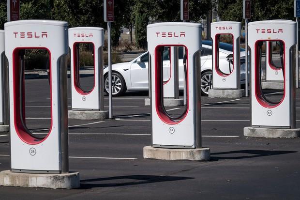 ガソリン車の墓標のように見えるテスラの充電ステーション(カリフォルニア、Bloomberg)
