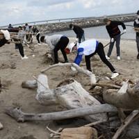 海岸に漂着したゴミや流木を片付ける外国人技能実習生ら=2020年11月28日午前9時44分、松本昌樹撮影
