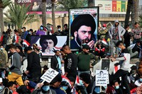 Followers of Shiite cleric Muqtada al-Sadr, in the posters, gather in Tahrir Square, Baghdad, Iraq, Friday, Nov. 27, 2020. (AP Photo/Khalid Mohammed)