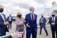 In this Oct. 5, 2020 file photo, Jill Biden moves her husband, Democratic presidential candidate former Vice President Joe Biden, back from members of the media as he speaks outside his campaign plane at New Castle Airport in New Castle, Del., to travel to Miami for campaign events. (AP Photo/Andrew Harnik)
