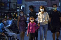 People wearing face masks to protect against the coronavirus, walk along a street in Hong Kong, on Nov. 30, 2020. (AP Photo/Kin Cheung)