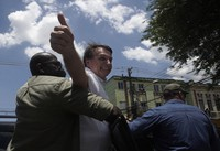 Brazil's President Jair Bolsonaro greets supporters after voting during the run-off municipal elections in Rio de Janeiro, Brazil, on Nov. 29, 2020. (AP Photo/Silvia Izquierdo)
