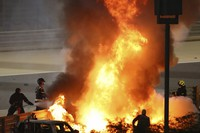 Staff extinguish flames from Haas driver Romain Grosjean of France's car after a crash during the Formula One race in Bahrain International Circuit in Sakhir, Bahrain, on Nov. 29, 2020. (Brynn Lennon, Pool via AP)