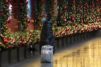 A shopper looks at Macy's window displays, on Nov. 30, 2020, in New York. (AP Photo/Mark Lennihan)