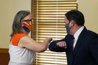 Arizona Secretary of State Katie Hobbs, left, and Arizona Gov. Doug Ducey bump elbows as they meet to certify the election results for federal, statewide, and legislative offices and statewide ballot measures at the official canvass at the Arizona Capitol on Nov. 30, 2020, in Phoenix. (AP Photo/Ross D. Franklin, Pool)