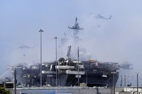 In this July 13, 2020 file photo helicopters approach the USS Bonhomme Richard as crews fight the fire in San Diego. The Navy on Nov. 30, 2020, said that it will decommission the warship docked off San Diego after suspected arson caused extensive damage, making it too expensive to restore. (AP Photo/Gregory Bull)