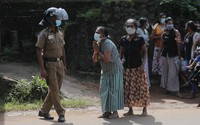 A family member of an inmate pleads to a policeman as she seeks information on the condition of her relative, outside the Mahara prison complex following an overnight unrest in Mahara, Sri Lanka, on Nov. 30, 2020. (AP Photo/Eranga Jayawardena)