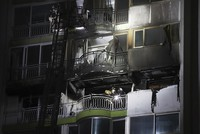 Firefighters inspect a damaged apartment after a fire in Gunpo, South Korea, on Dec. 1, 2020. (Hong Ki-won/Yonhap via AP)