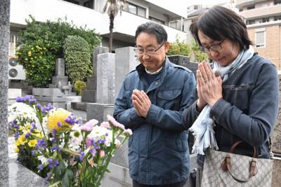 笹子トンネル事故で亡くなった森重之さんの墓の前で手を合わせる父和之さん(左)と母美世さん=東京都文京区で11月27日、金子昇太撮影