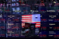In this March 16, 2020 file photo, a United States flag is reflected in the window of the Nasdaq studio, which displays indices and stocks down, in Times Square, New York.  (AP Photo/Seth Wenig)