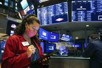 In this photo provided by the New York Stock Exchange, trader Ashley Lara uses her handheld device as she works on the trading floor, on Dec. 1, 2020. (Colin Ziemer/New York Stock Exchange via AP)