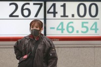 A woman walks by an electronic stock board of a securities firm in Tokyo on Dec. 2, 2020. (AP Photo/Koji Sasahara)