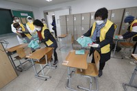 Health officials disinfect the desks as a precaution against the coronavirus for the upcoming college entrance exams in a classroom at a high school in Seoul, South Korea, on Dec. 1, 2020. (AP Photo/Ahn Young-joon)