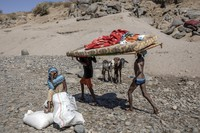 Tigray refugees who fled the conflict in the Ethiopia's Tigray carry their furniture on the banks of the Tekeze River on the Sudan-Ethiopia border, in Hamdayet, eastern Sudan, on Dec. 1, 2020. (AP Photo/Nariman El-Mofty)