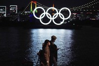 A man and a woman walk past near the Olympic rings floating in the water in the Odaiba area on Dec. 1, 2020, in Tokyo. (AP Photo/Eugene Hoshiko)