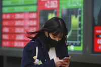 A woman walks by an electronic stock board of a securities firm in Tokyo, on Dec. 2, 2020. (AP Photo/Koji Sasahara)