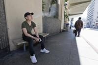 In this June 17, 2019 file photo, a man takes a vaping break from his job at a smoke shop in San Francisco. (AP Photo/Samantha Maldonado)
