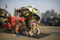 Protesting farmers, Raghuvir Singh, right, and Gurnam Singh bask in the morning sun while sitting next to their tractor parked on a highway, during a protest at the Delhi-Haryana state border, India, on Dec. 1, 2020. (AP Photo/Altaf Qadri)