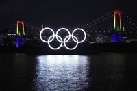 The Olympic rings float in the water with town's landmark