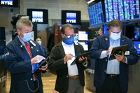 In this photo provided by the New York Stock Exchange, traders James Lamb, Sal Suarino and John Santiago, left to right, work on the trading floor, on Dec. 3, 2020. (Nicole Pereira/New York Stock Exchange via AP)