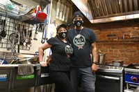Owners of The Black Italian restaurant and catering service, Paula Hunter, left, and her husband Anthony Hunter are seen in their empty restaurant in Louisville, Ky., on Dec. 3, 2020. (AP Photo/Timothy D. Easley)