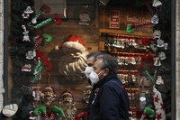 People walk past a shop window adorned with Christmas decorations in Rome on Dec. 1, 2020. (AP Photo/Gregorio Borgia)