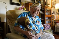 Mickey Ganitch, a 101-year-old survivor of the attack on Pearl Harbor, holds a football statue he was given, in the living room of his home in San Leandro, California, Nov. 20, 2020. (AP Photo/Eric Risberg)