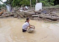 A young girl washes a pillow in flood water near ruins of houses at a neighborhood affected by the flood in Medan, North Sumatra, Indonesia, on Dec. 4, 2020. (AP Photo/Binsar Bakkara)
