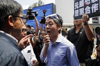 In this Aug. 12, 2019, file photo, pro-democracy lawmaker Ted Hui, center, argues with pro-Beijing lawmaker Junius Ho, left, during a demonstration in Hong Kong. (AP Photo/Kin Cheung)