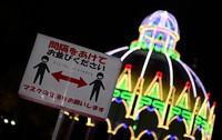 A sign warning people to take preventative measures against coronavirus transmission is seen near the Cassa Armonica light installation in Kobe East Park in Kobe's Chuo Ward, on Dec. 4, 2020. (Mainichi/Tatsuya Fuji)