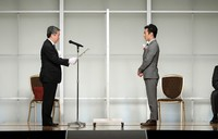 Racing driver Takuma Sato, who won the Mainichi sporting figure grand prix, is seen on stage to accept his award from Mainichi Newspapers Co. President Masahiro Maruyama, left, in Tokyo's Bunkyo Ward on Dec. 4, 2020, while a partition is set up between the two. (Mainichi/Masahiro Ogawa)