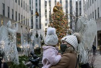 A woman holds her daughter as they look at the Rockefeller Center Christmas Tree on Dec. 3, 2020 in New York. (AP Photo/Mark Lennihan)