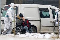 Medical workers wearing protective gear transport a patient suspected of having novel coronavirus in a wheelchair at a hospital in Kommunarka, outside Moscow, Russia, on Dec. 3, 2020. (AP Photo/Alexander Zemlianichenko Jr)