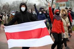 ベラルーシ大統領選の不正を訴える抗議デモでルカシェンコ政権への抵抗の象徴である旧国旗を掲げる市民=ミンスクで2020年11月22日、AP